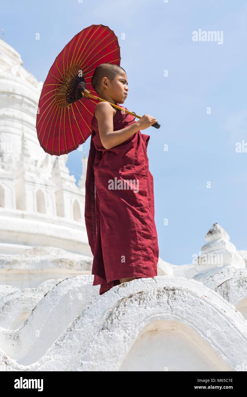 Young novice Buddhist monk holding parasol at Myatheindan Pagoda (also known as Hsinbyume Pagoda), Mingun, Myanmar Stock Photo