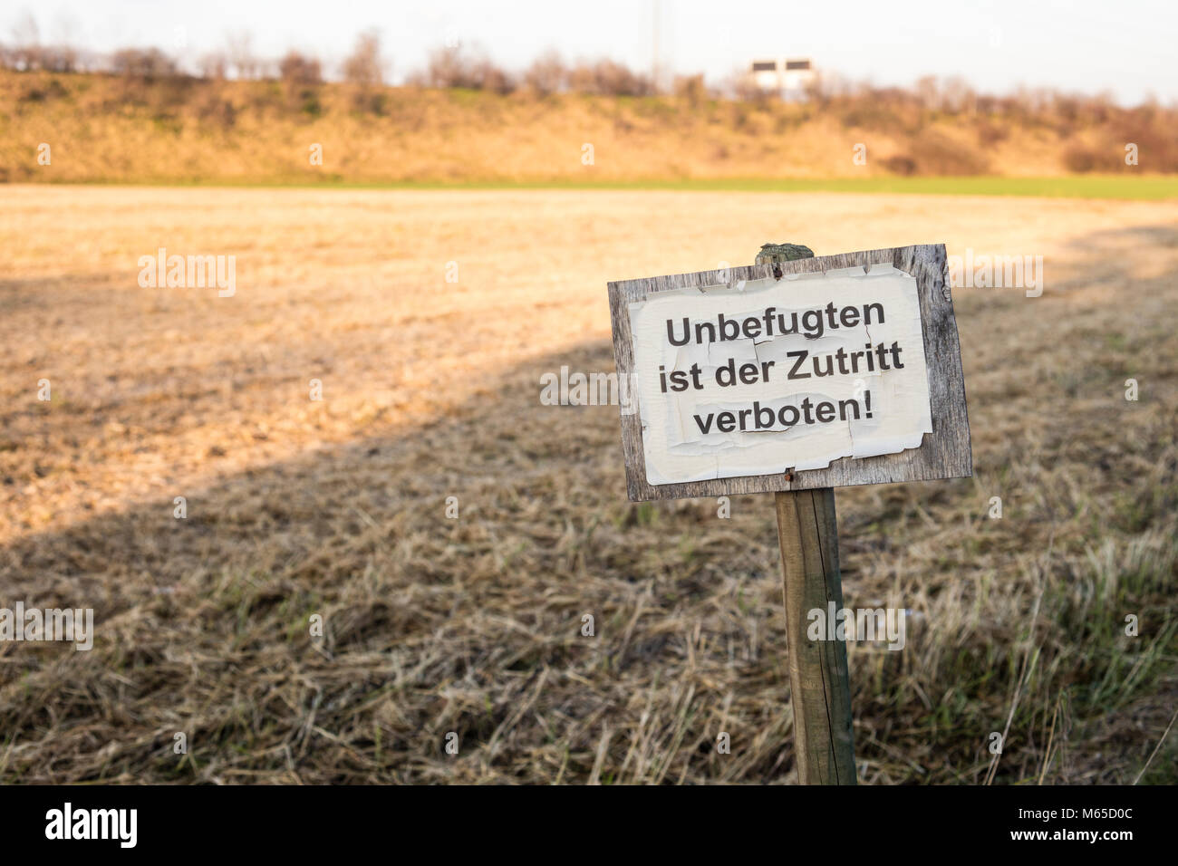 Grunge and old signboard in countryside's crop field with text in german meaning: 'Access to people without - Stock Image