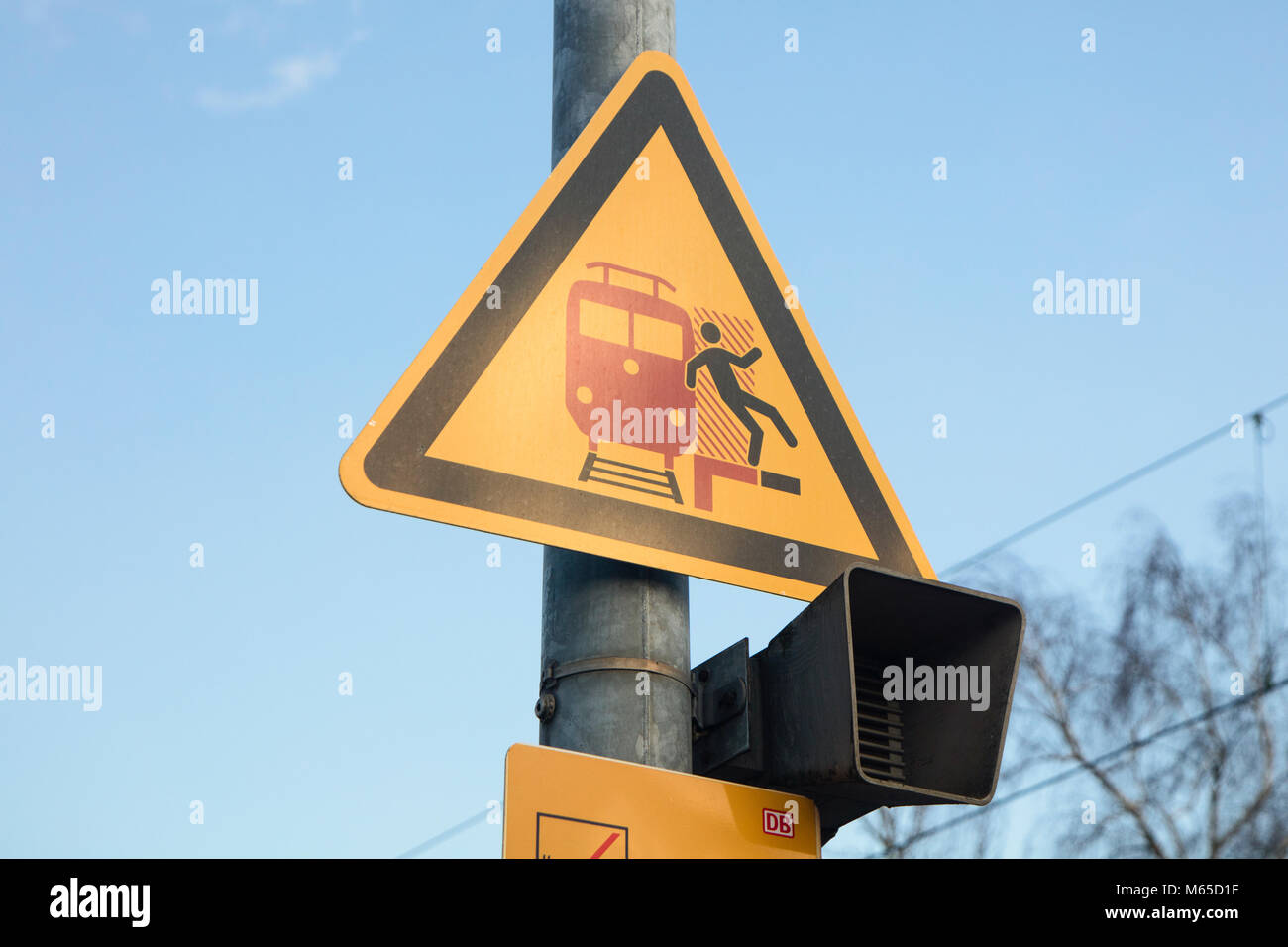 Signboard in german train station, bewaring people paying attention when train comes and not falling in rail tracks. - Stock Image