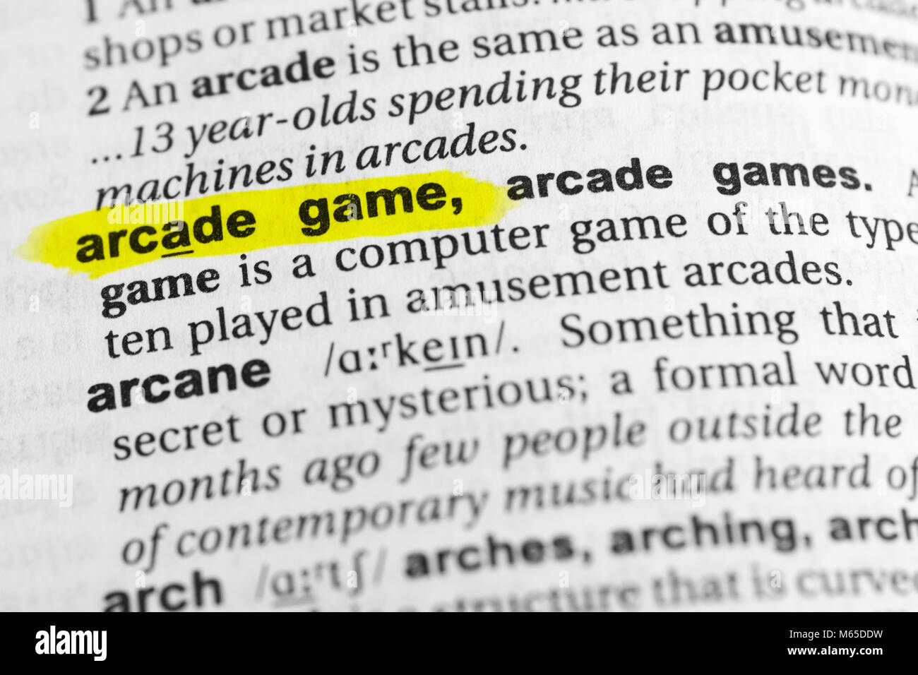Highlighted English word 'arcade game' and its definition in the dictionary. - Stock Image