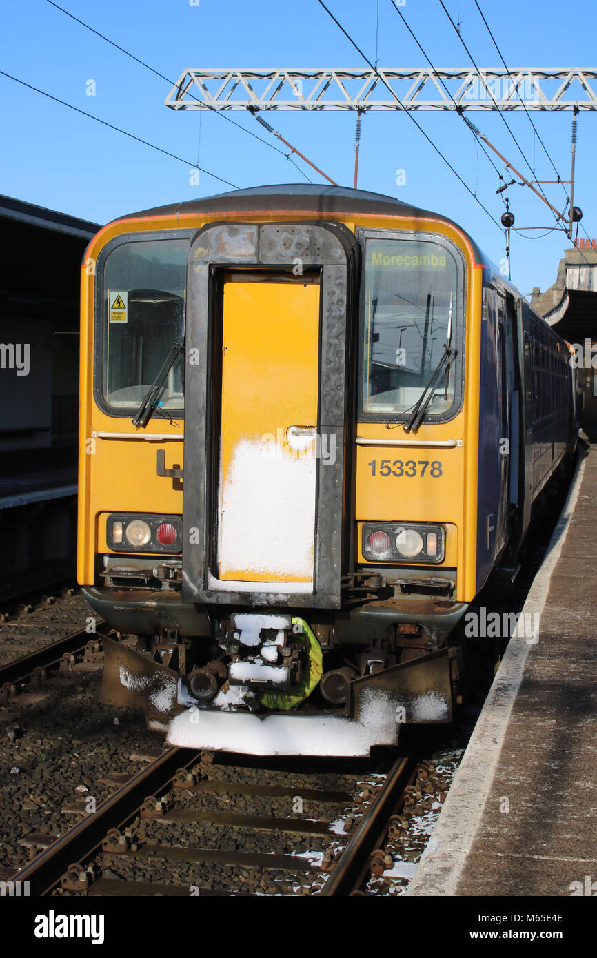 Class 153 single car Super Sprinter unit in Northern livery at Carnforth station, platform 1 with a passenger service - Stock Image