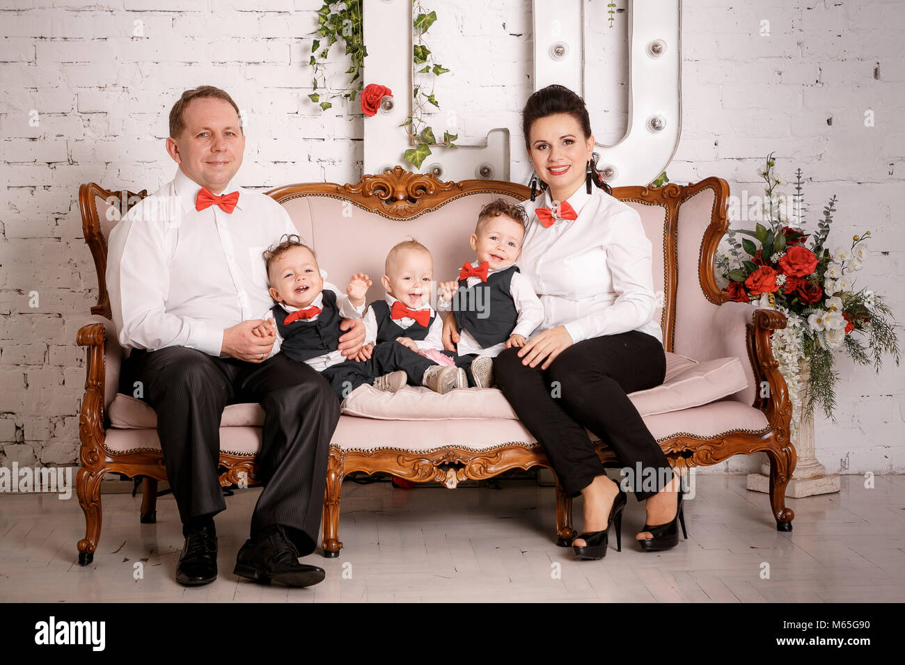 Big happy family: mother, father, triplets sons - Stock Image