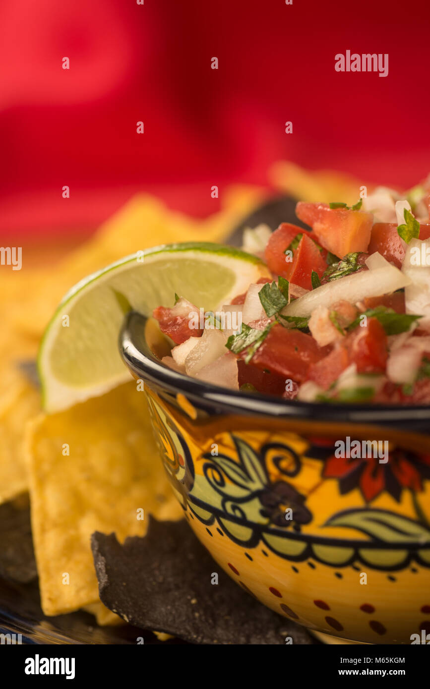 Pico De Gallo in a pretty Ethnic bowl with blue corn and white corn tortilla chips against red background Stock Photo