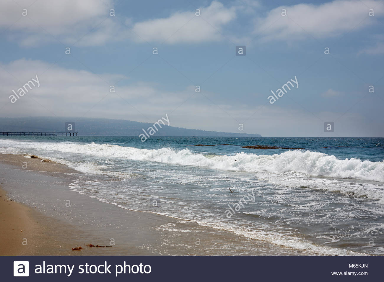 Overcast, Blue Sky and water waves on the sandy Coast of Pacific Ocean, Manhattan Beach Southern California - Stock Image