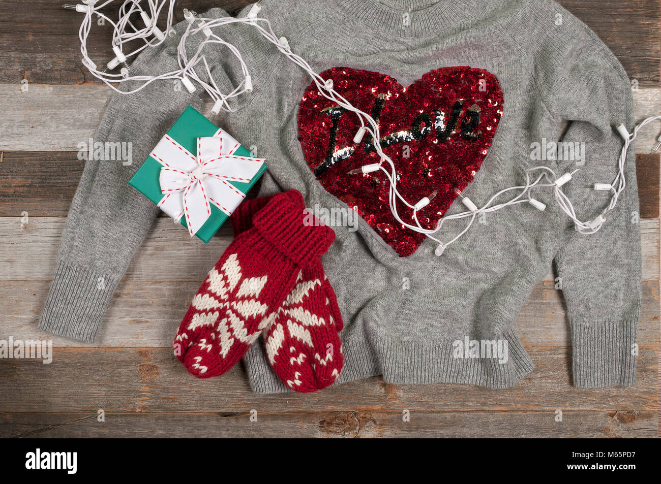 Christmas presents laid on a wooden table background. Winter clothes warm sweater and knitted mittens near gift - Stock Image