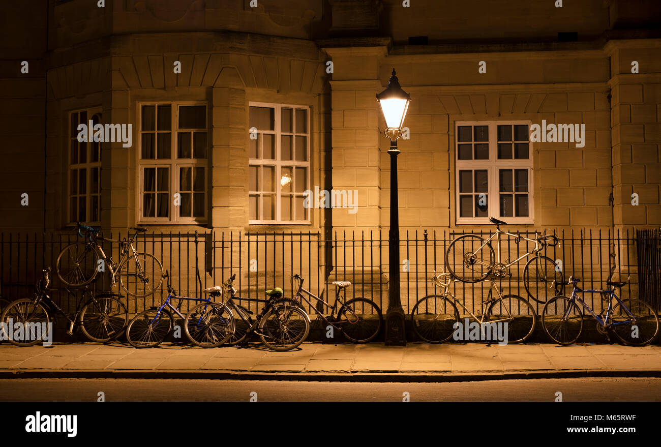 Students bicycles against the railings infront of a college building at night. Oxford, Oxfordshire, England - Stock Image