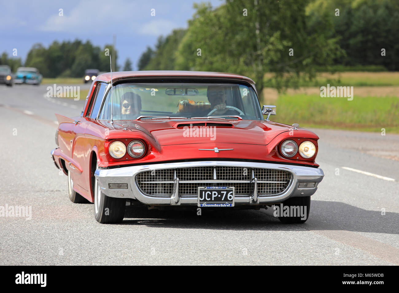 SOMERO, FINLAND - AUGUST 5, 2017: Red Thunderbird hardtop 1960 classic car moves along rural highway on Maisemaruise Stock Photo