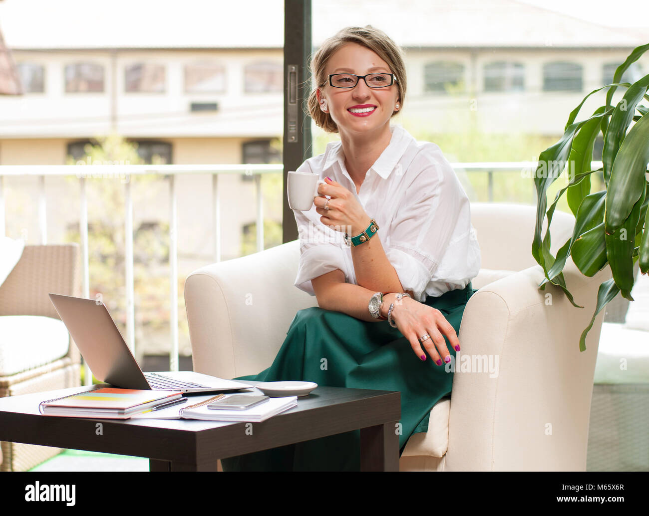 Happy business woman drinks coffee, enjoying espresso sitting at her working place in office - Stock Image