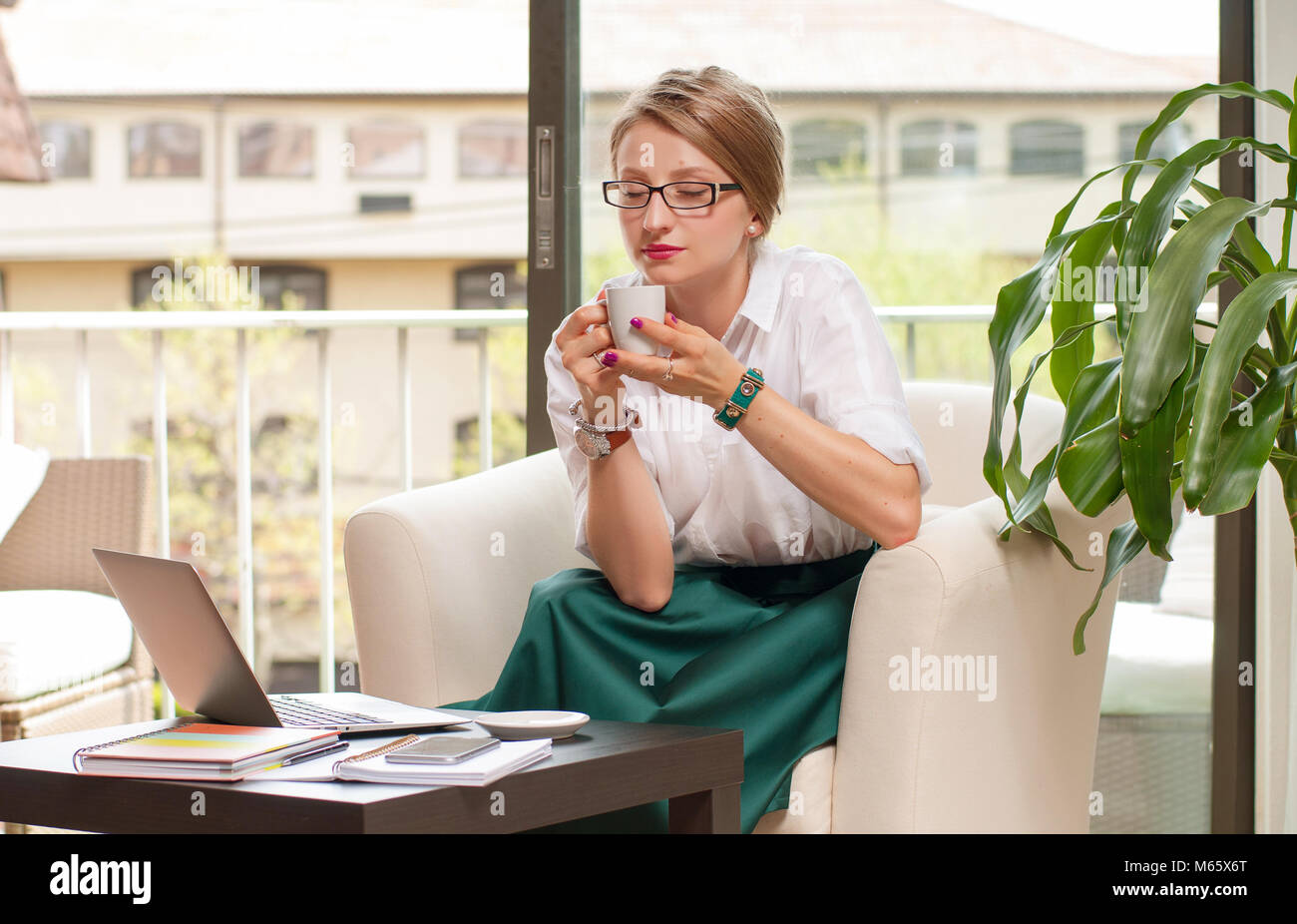 Business woman drinks coffee, enjoying espresso sitting at her working place in office Stock Photo