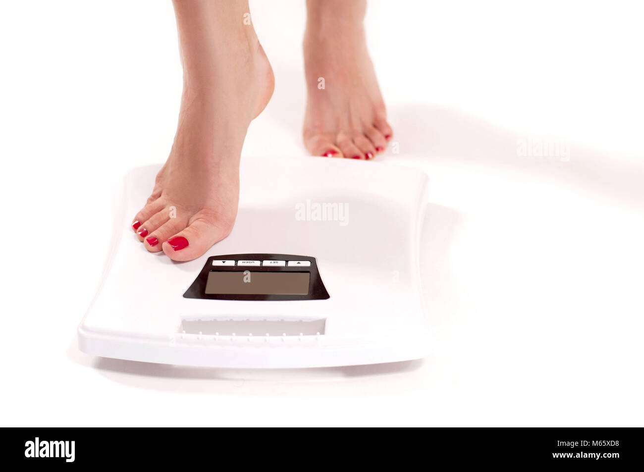 Diet and Weight Loss. Woman standing on weight scale - Stock Image