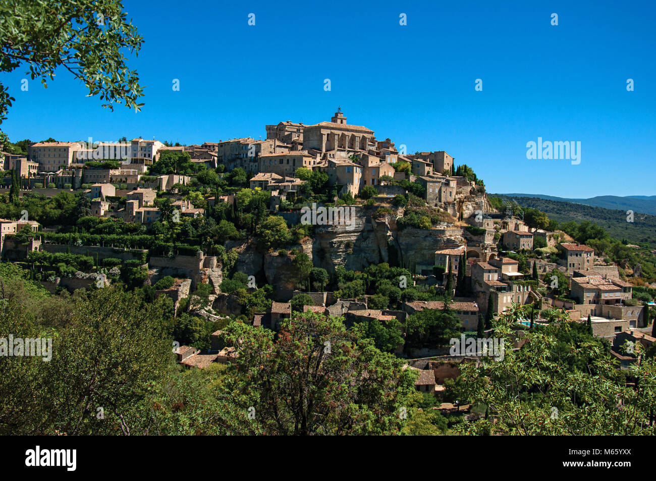 Panoramic view of the village of Gordes on top of a hill and under sunny blue sky. Located in the Provence region, Stock Photo