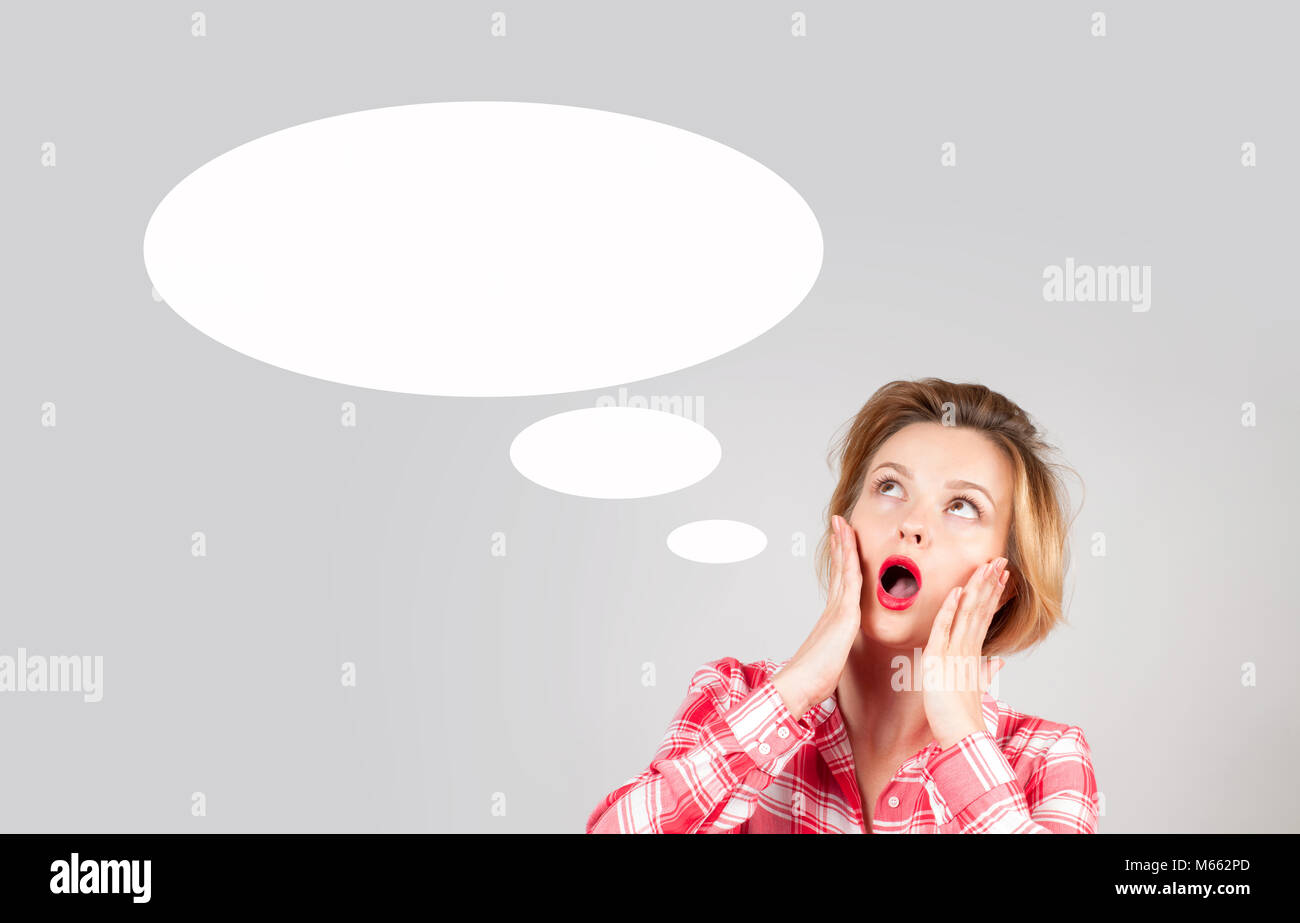 Portrait of business woman with empty speech bubbles, looking up. Idea concept - Stock Image