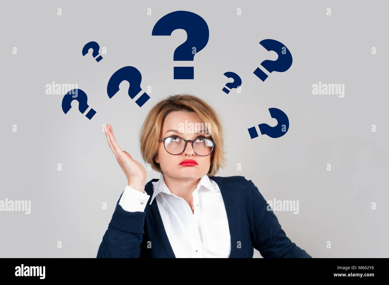 Thinking woman with questioning expression and question marks above her head - Stock Image