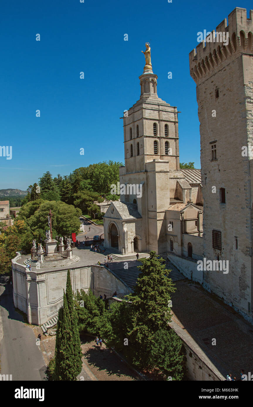 Church with steeple tower next to the Palace of the Popes of Avignon, under a sunny blue sky. Located in the Provence - Stock Image