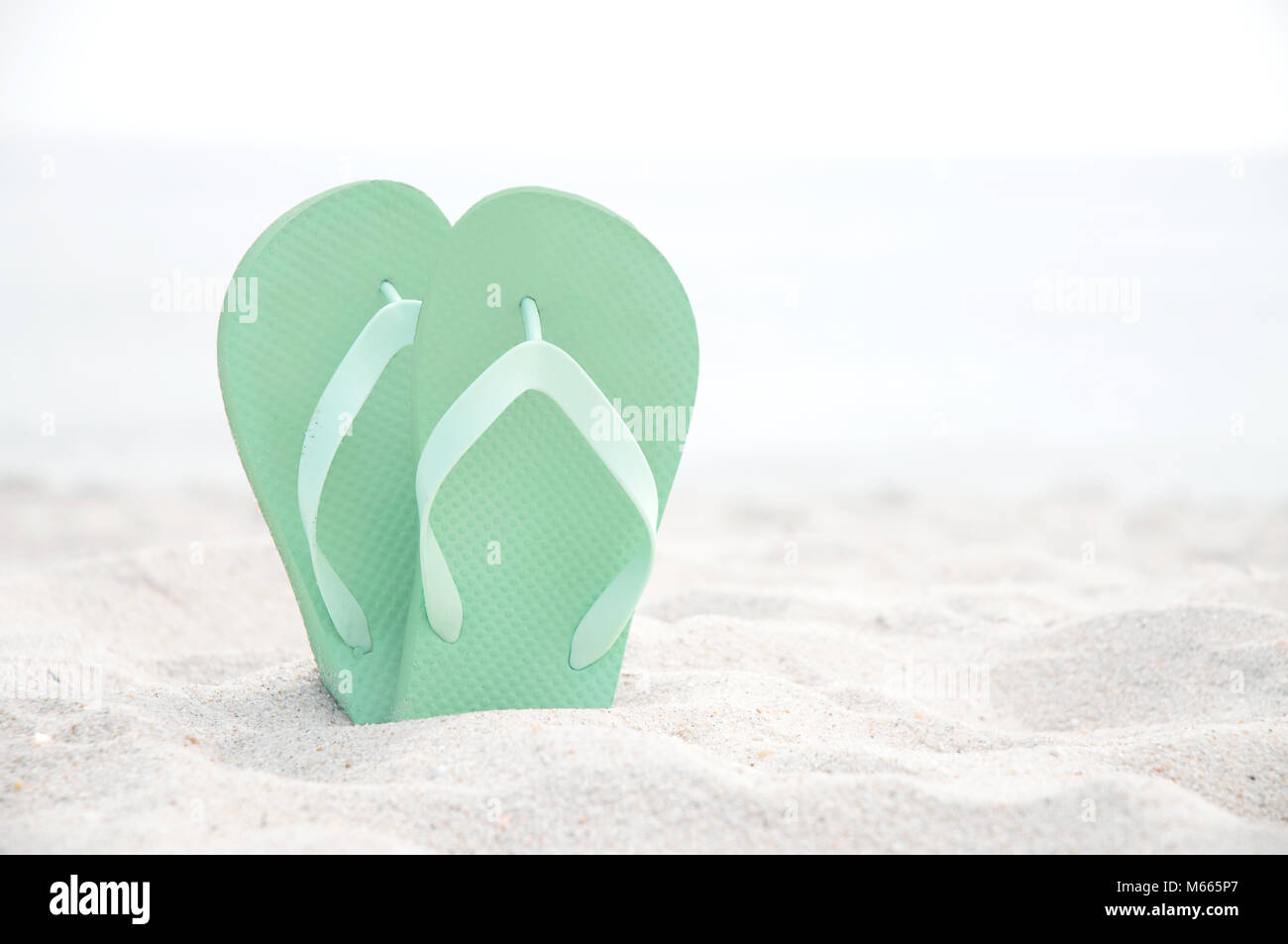 Flip flop on the white sand beach. Summer vacations - Stock Image