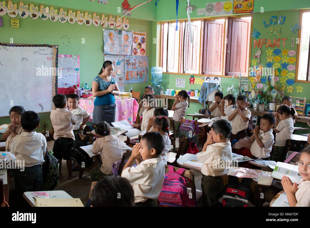 Yucatec Maya school children praying in their classroom with their teacher. San Antonio, Cayo District, Belize. - Stock Image