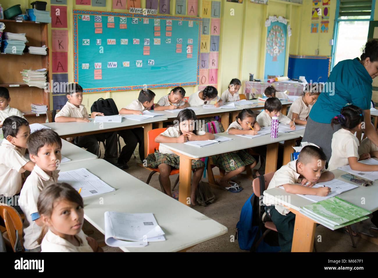 Yucatec Maya school children studying in their classroom with their teacher. San Antonio, Cayo District, Belize. - Stock Image