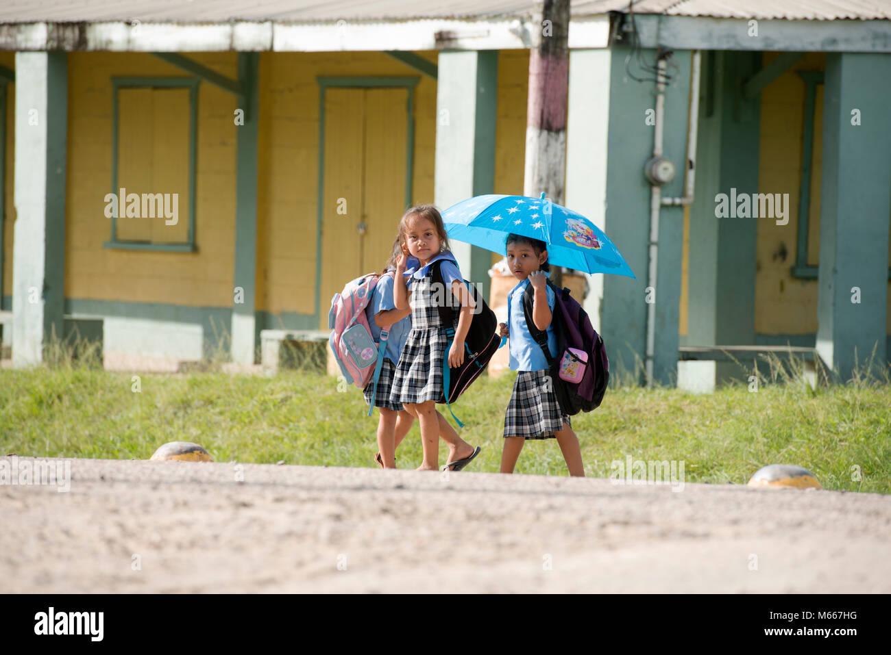 Ethnic, indigenous Yucatec Maya school children walking home from school. San Antonio, Cayo District, Belize. - Stock Image