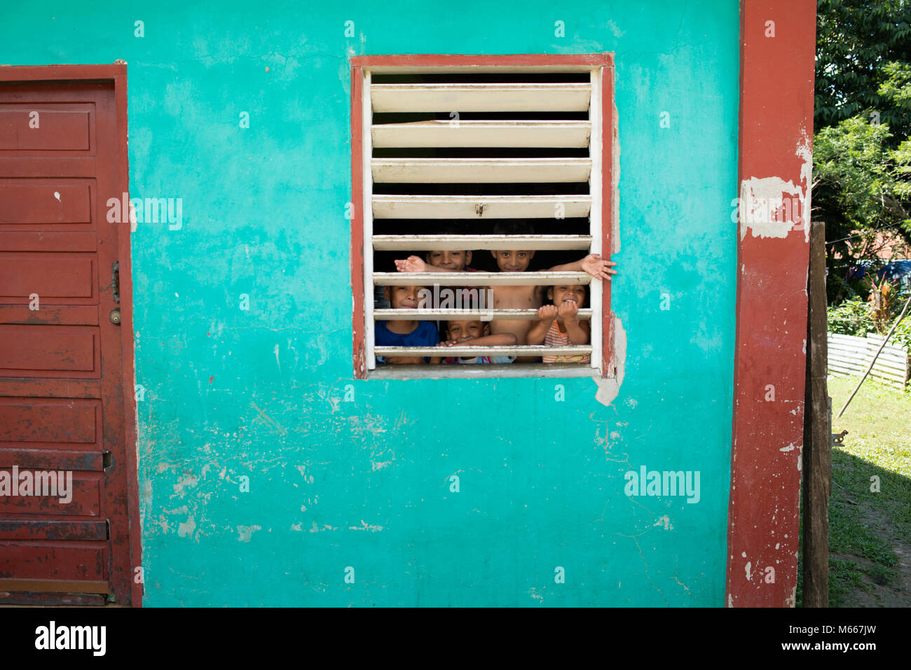 Indigenous Yucatec Maya children in their house, looking through a window. San Jose Succotz, Cayo District, Belize. - Stock Image