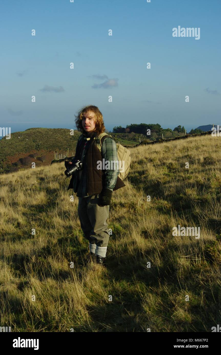 Young Ruggedly Handsome Outdoorsman with Long Blonde Hair Photographing The Valley of the Rocks, Exmoor National - Stock Image