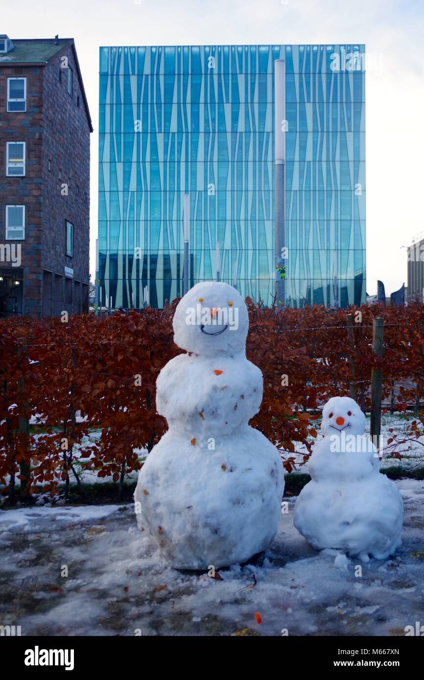 Pair of Snowmen in Academia Plaza with the Sir Duncan Rice Library Dominating the Background. University of Aberdeen, - Stock Image