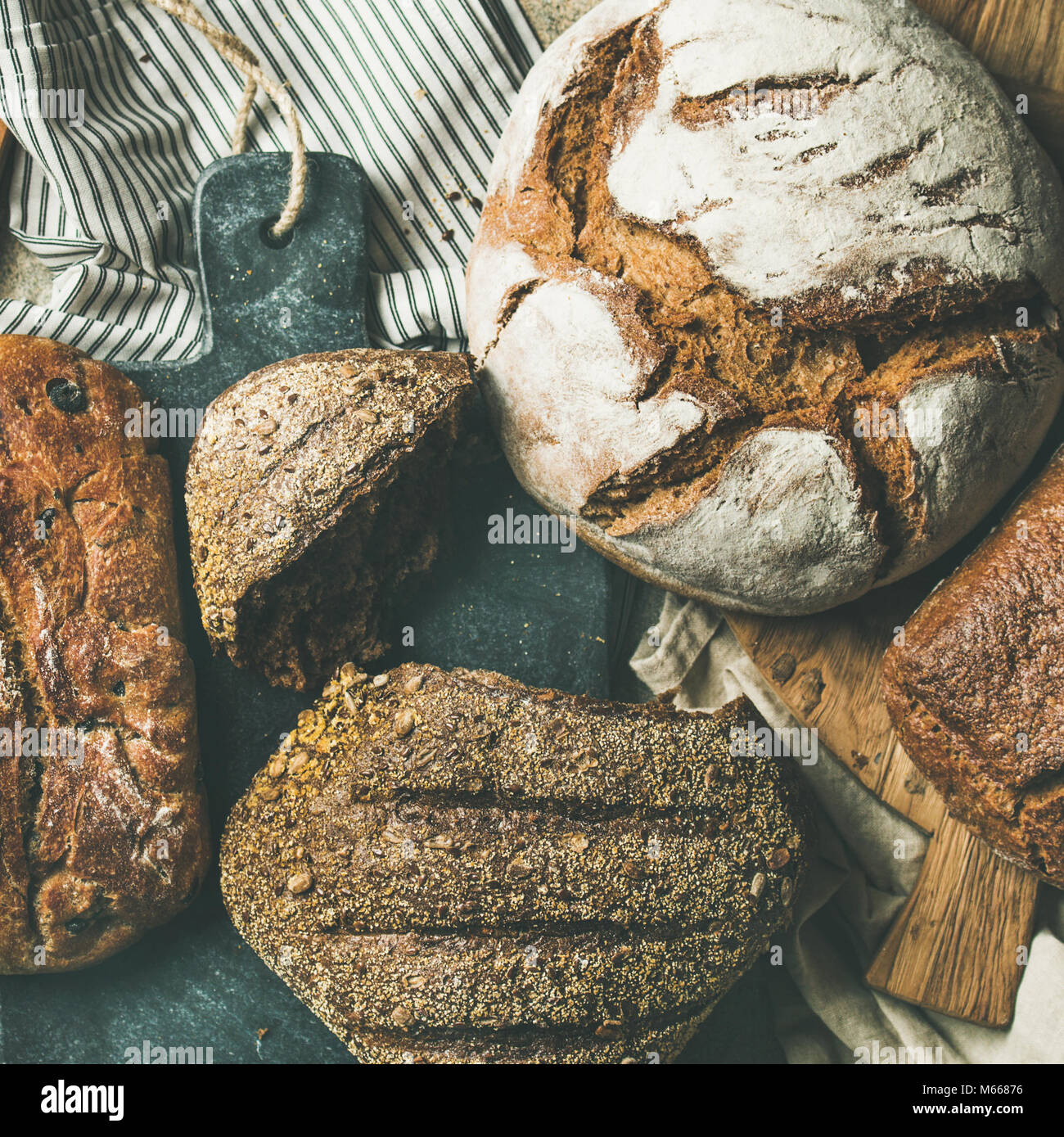 Flat-lay of various bread loaves on grey background, square crop Stock Photo