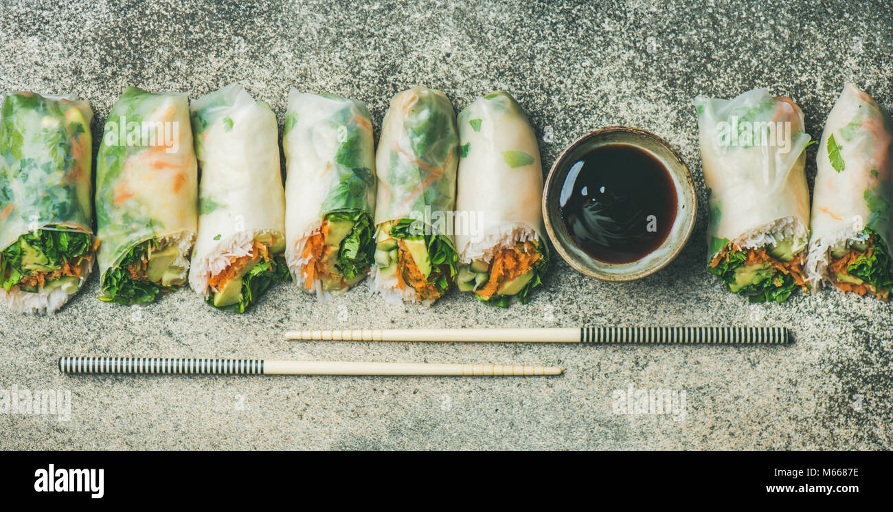 Vegan spring rice paper rolls over concrete background, wide composition - Stock Image