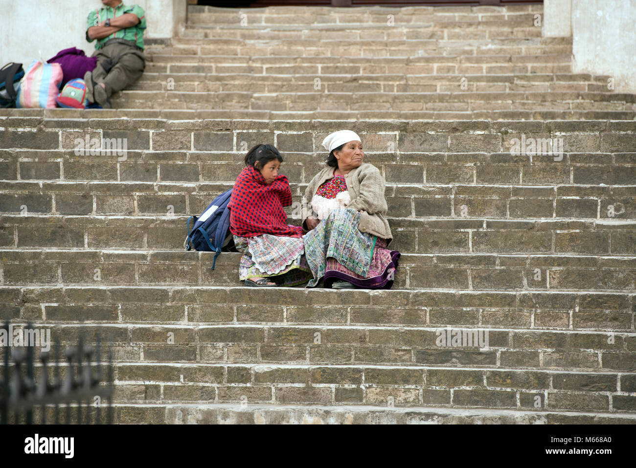 An ethnic, indigenous K'iche' (Quiché) Maya woman and child in traditional dress sitting on the steps - Stock Image