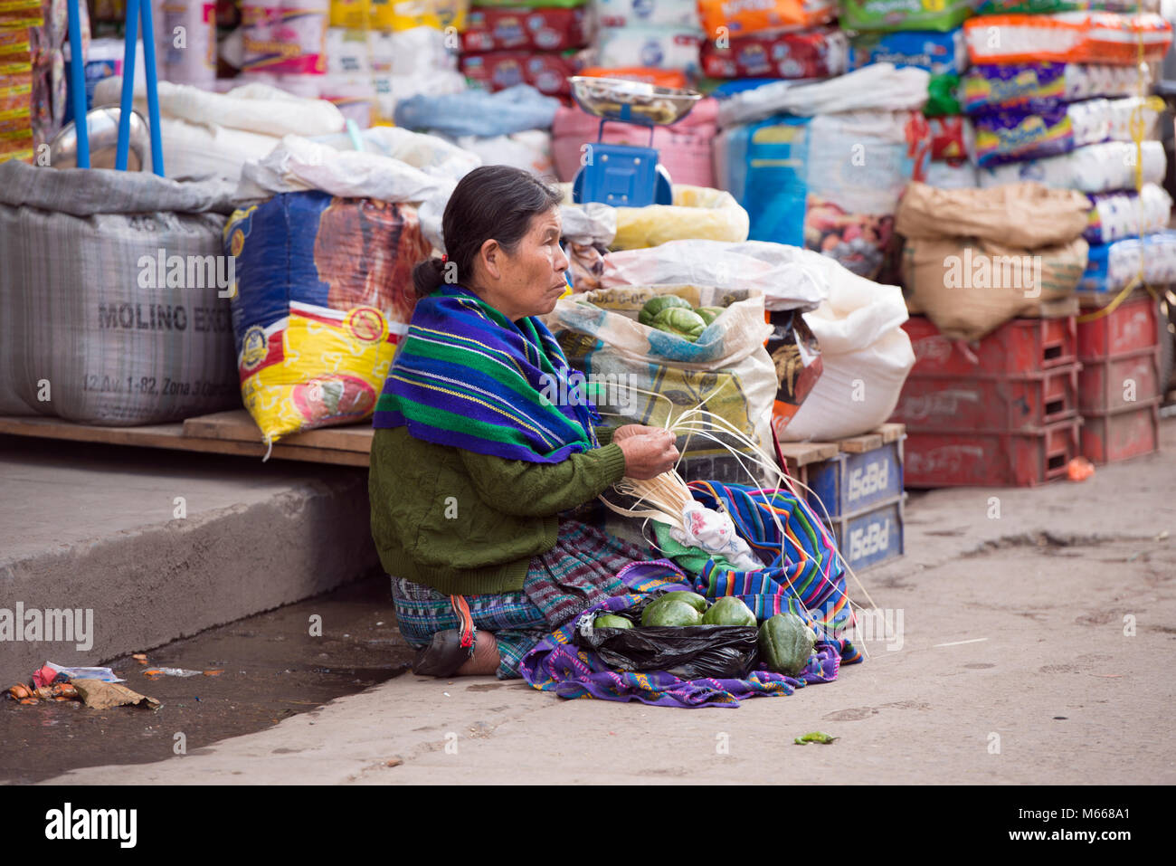 An ethnic, indigenous K'iche' (Quiché) Maya woman in traditional dress at the market. Santa Cruz del - Stock Image