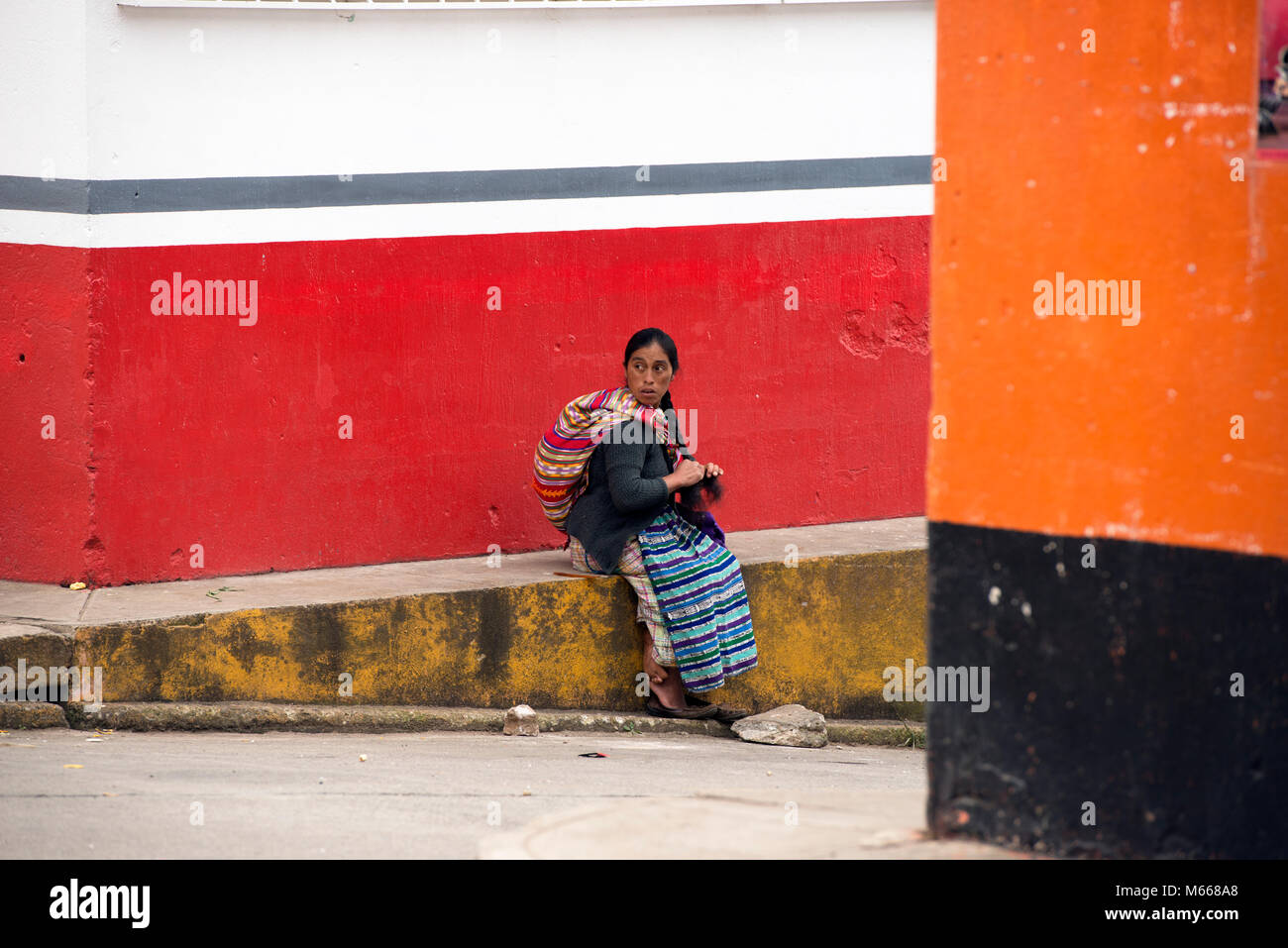 An indigenous, ethnic K'iche' (Quiché) Maya woman in traditional clothes sitting on a wall taking a - Stock Image