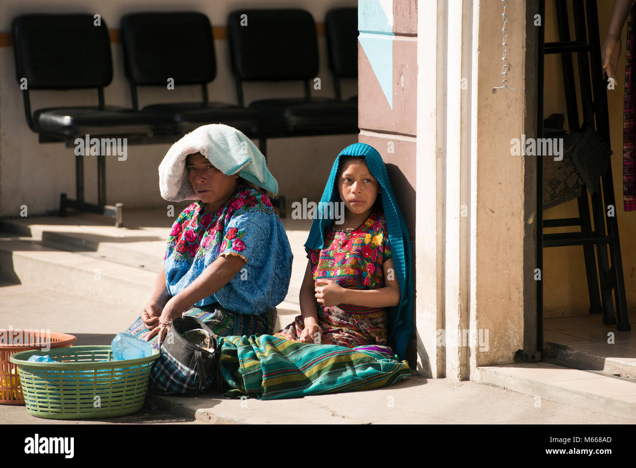 An indigenous K'iche' (Quiché) Maya woman and her daughter selling food in the market. Santa Cruz del - Stock Image