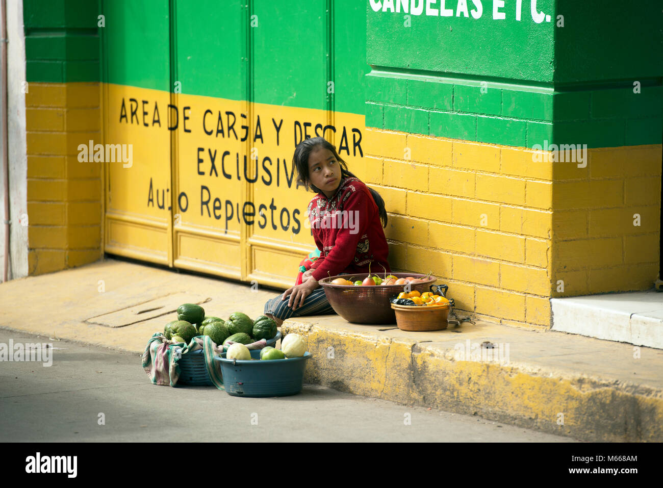 A young, indigenous K'iche' (Quiché) Maya girl in traditional dress selling fruit and vegetables in - Stock Image