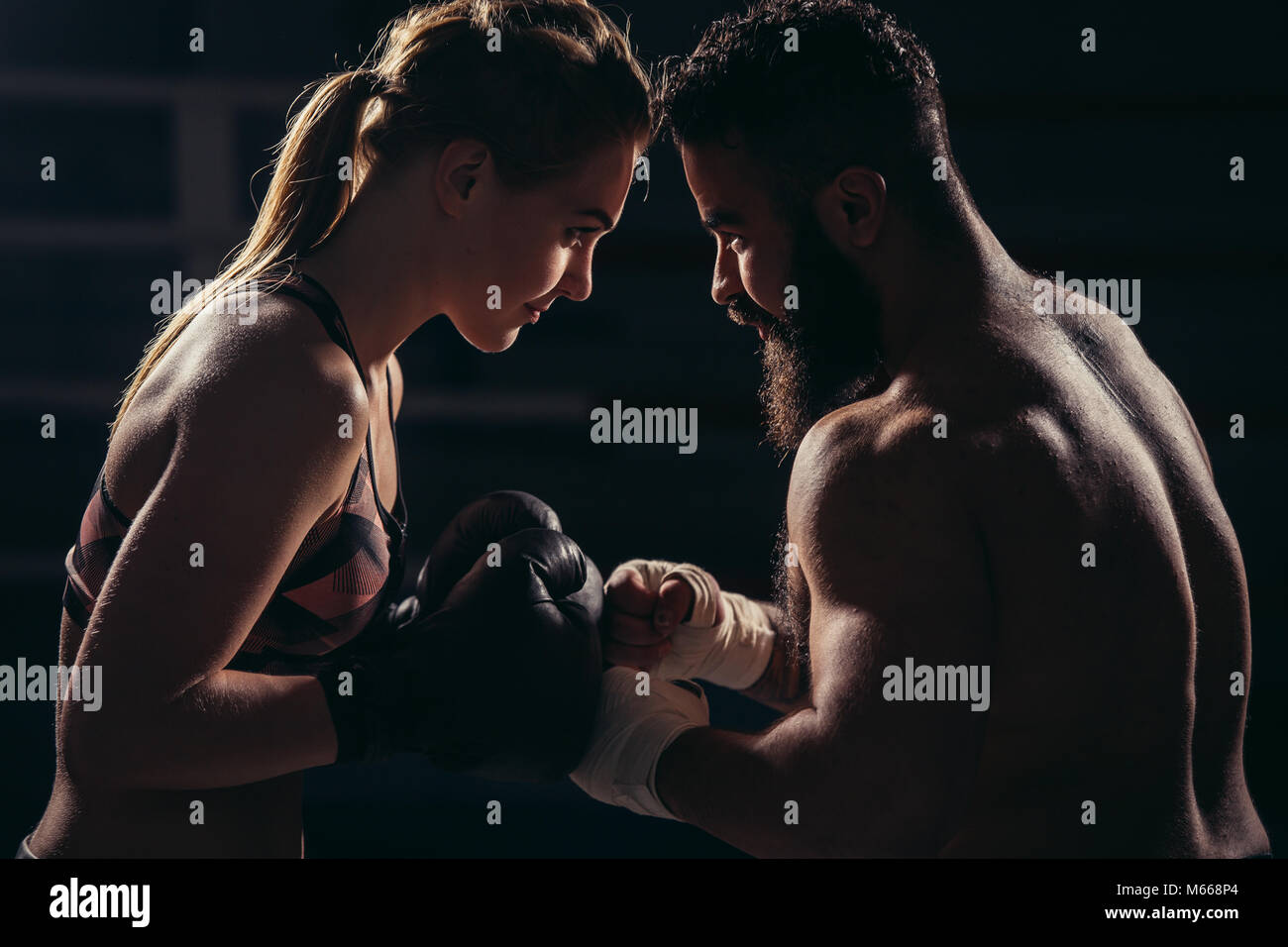 boxers with fighting stance against black background - Stock Image