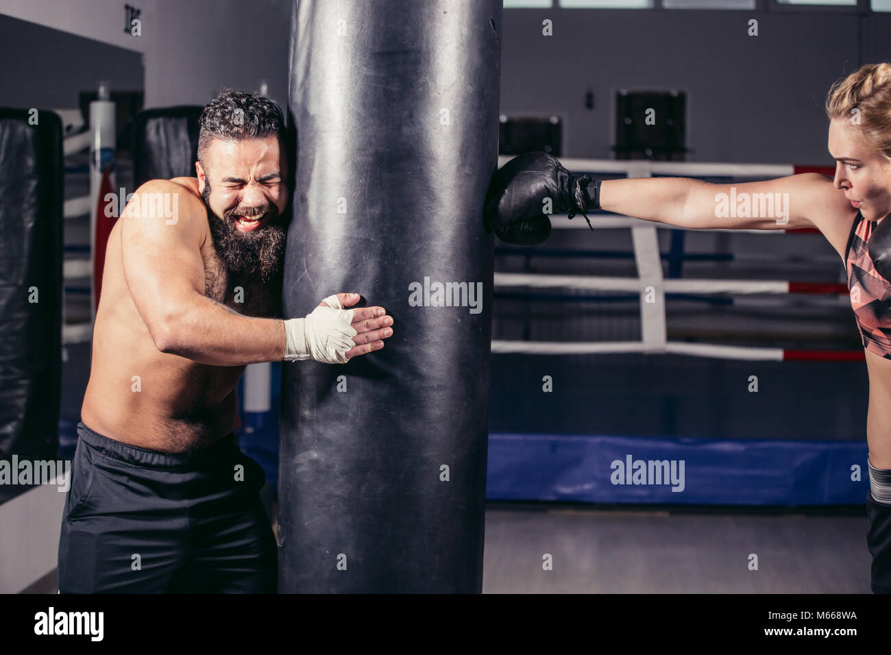 woman working out with boxing gloves and punching bag with her trainer. - Stock Image