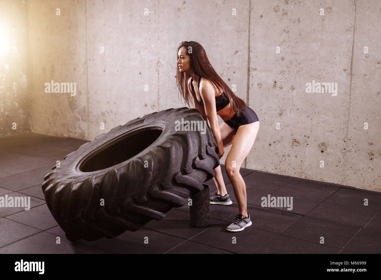 brunette flipping big tire in gym - Stock Image
