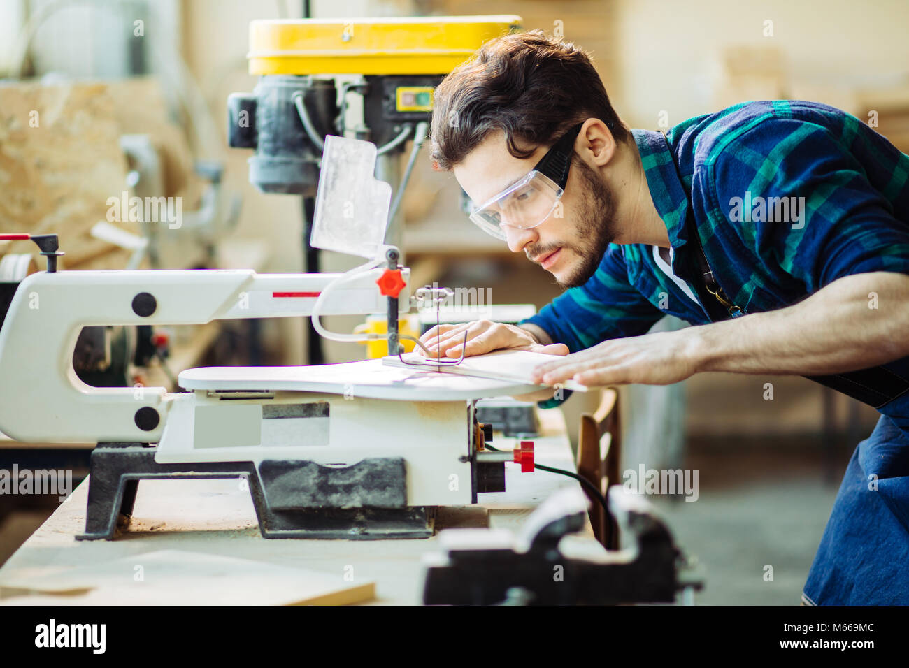 Carpenter engaged in processing wood at the sawmill. Stock Photo