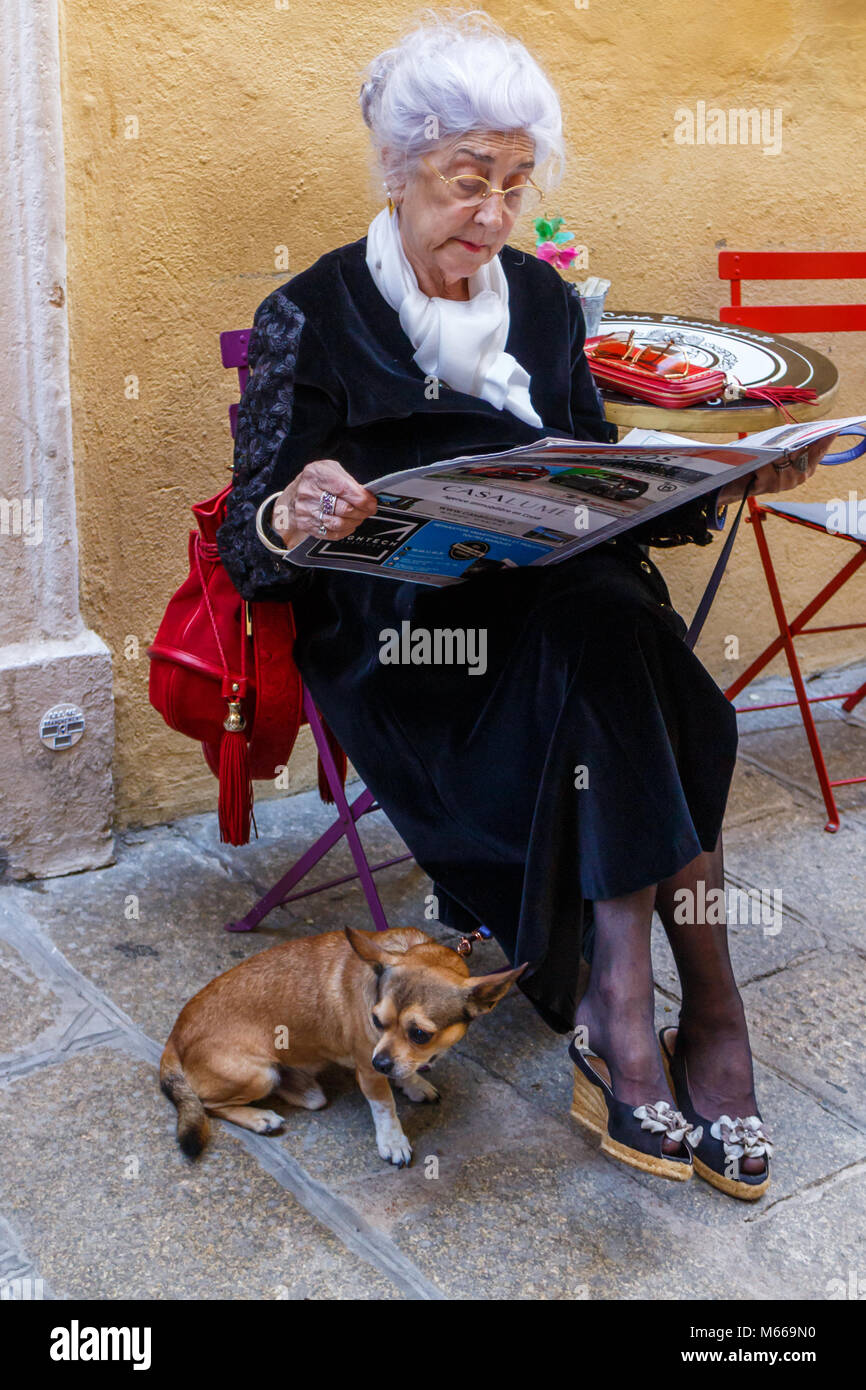 Elderly French lady with companion dog sitting reading