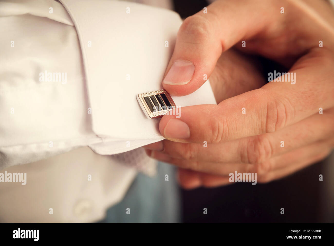 groom putting on cuff-links as he gets dressed in formal wear close up - Stock Image