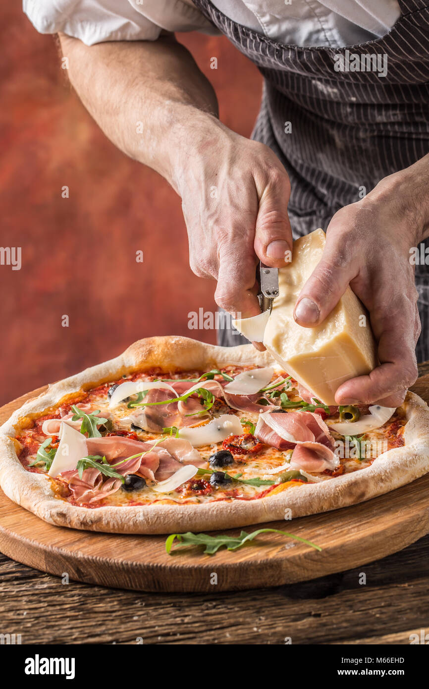 Pizza and Chef. Chef in the restaurant prepares a pizza and decorates it with parmesan cheese. - Stock Image