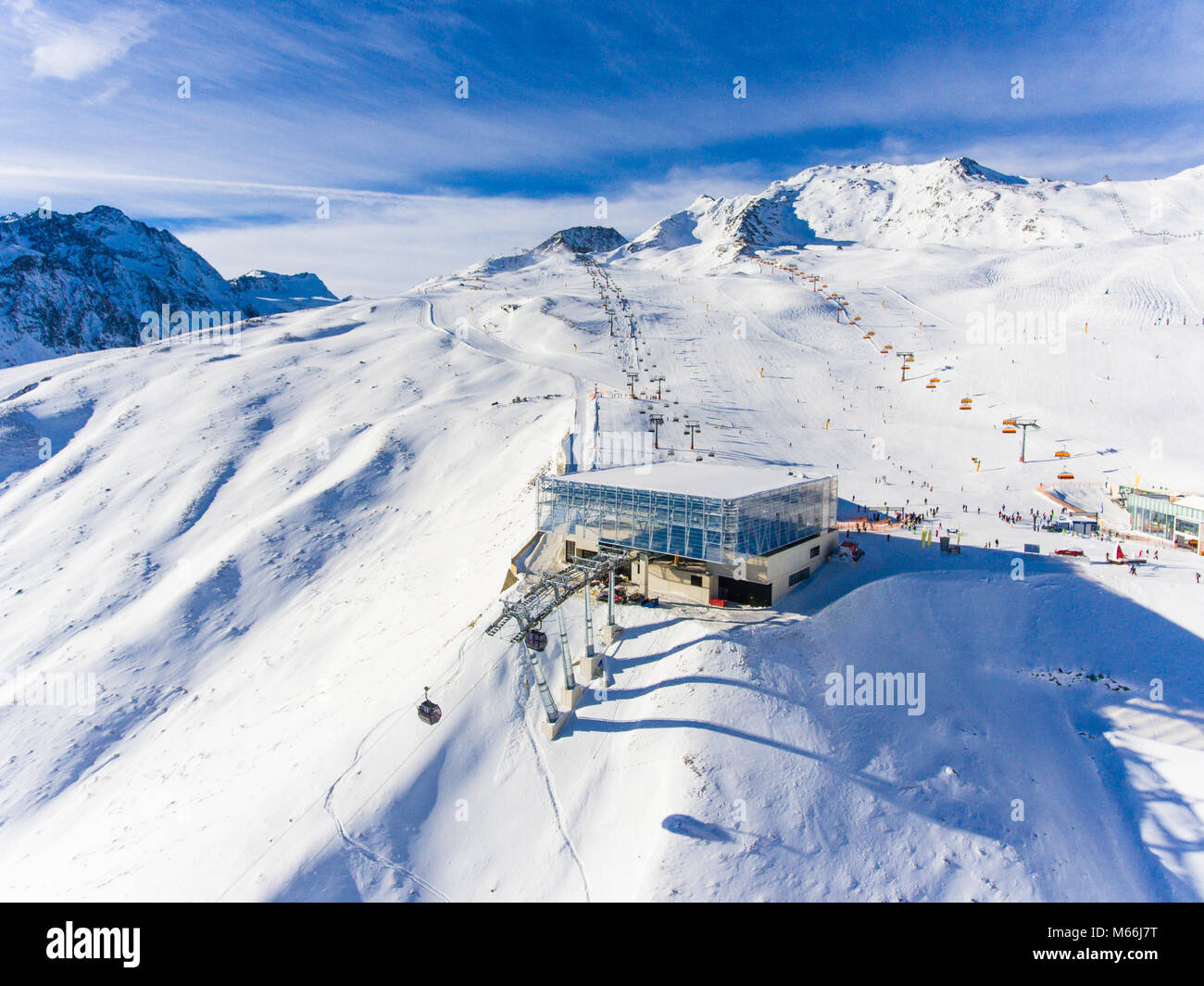 Ski resort in the Alps with ski lift and people skiing on the slope. Aerial view - Stock Image
