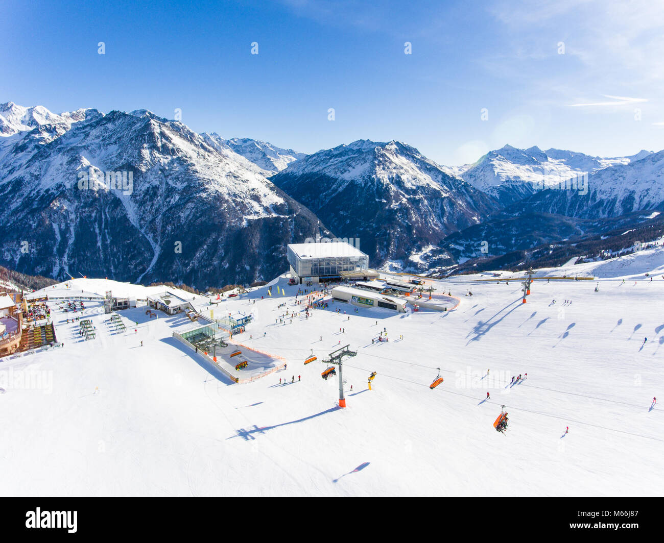 Panoramic aerial view of ski resort in the Alps with ski lift and people skiing on the slope - Stock Image