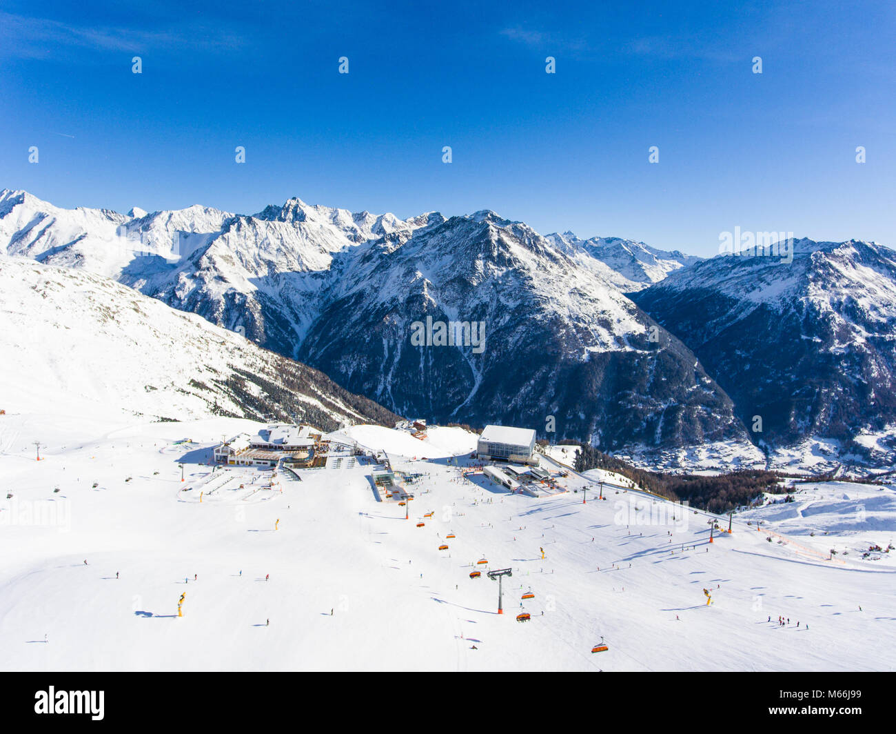 Aerial view of ski resort in the Alps with ski lift and people skiing on the slope - Stock Image