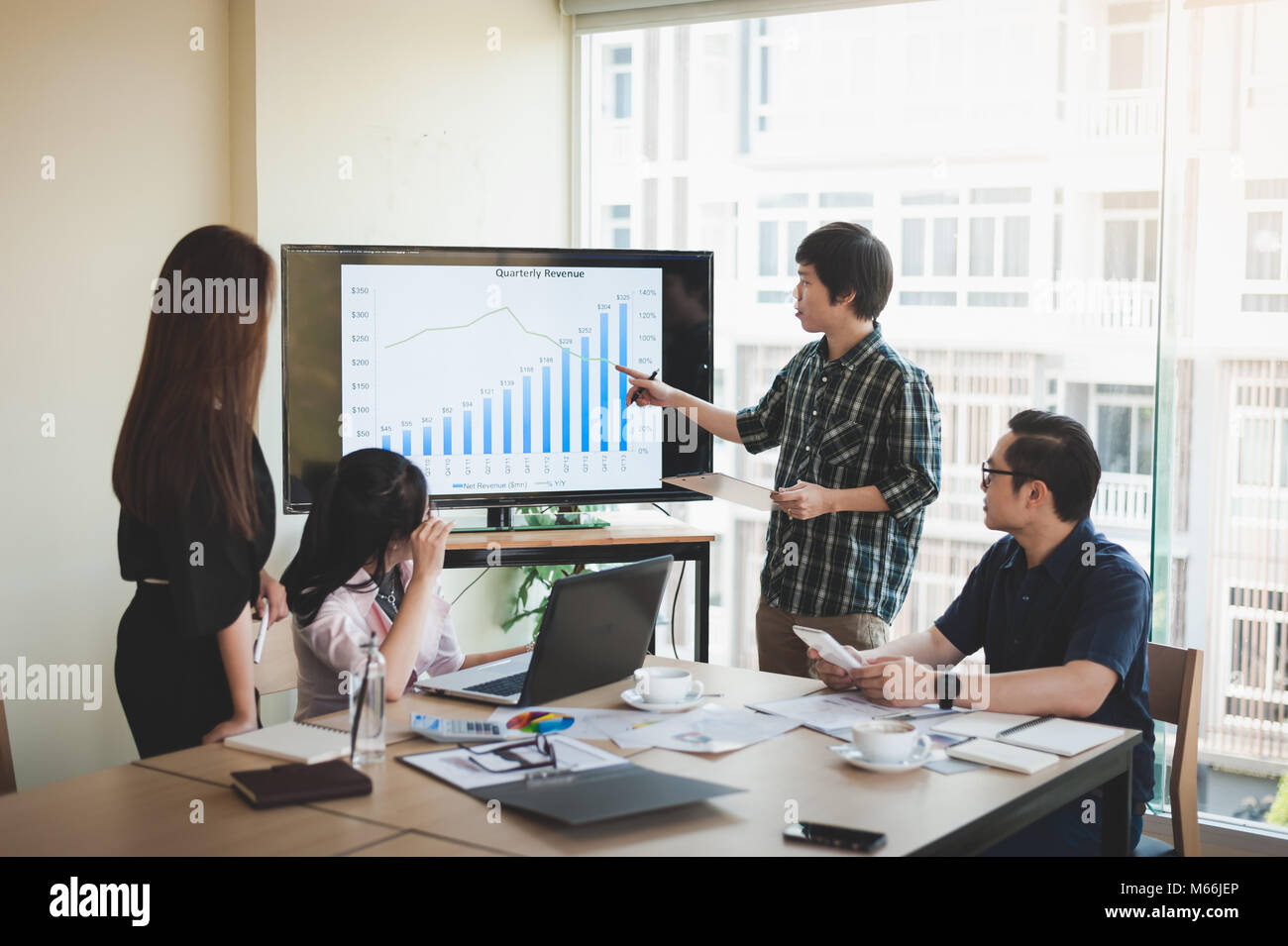 Asian businesswoman discussing and brainstorm with young freelance man in meeting room. Business company co-operate - Stock Image