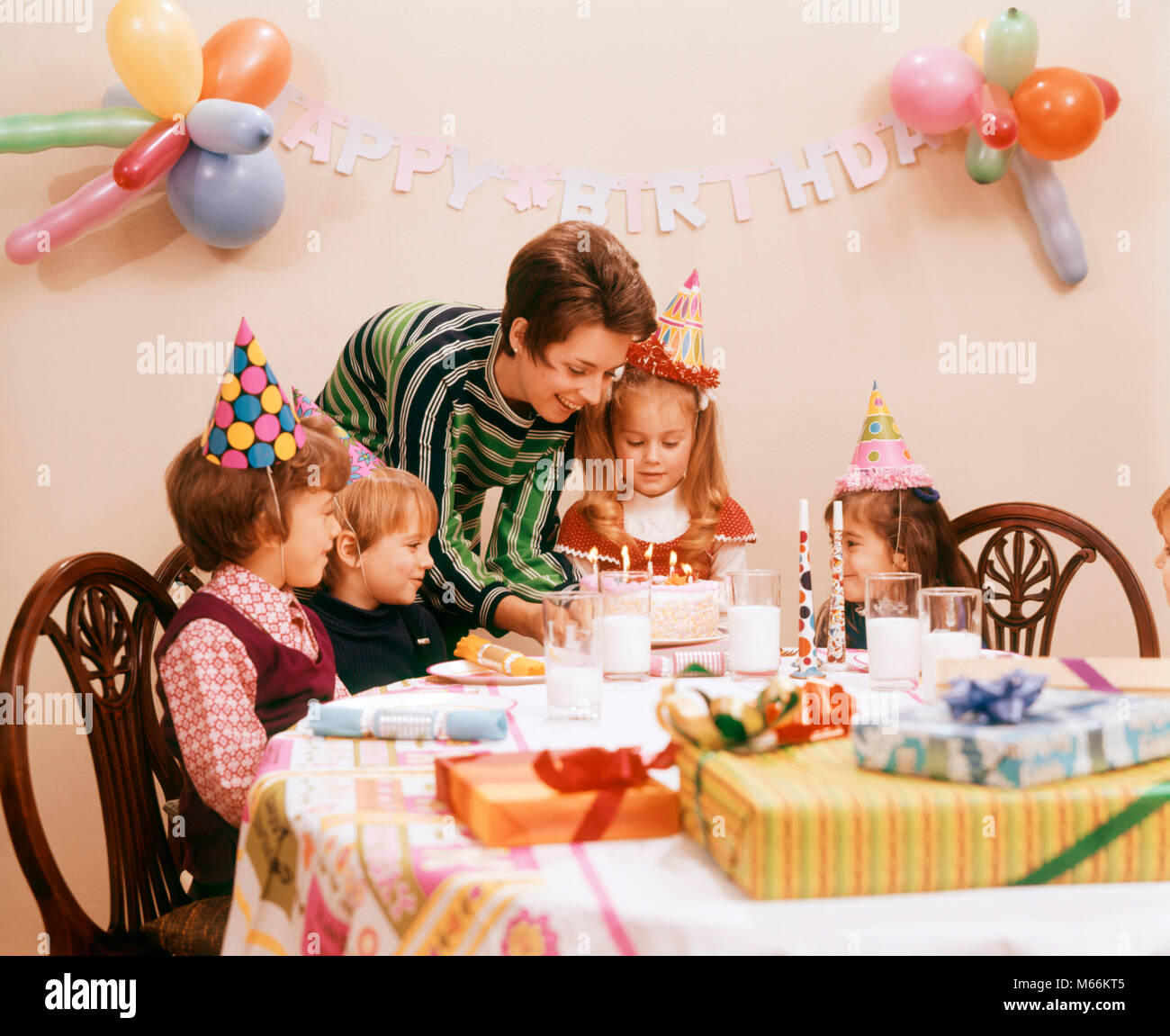 1970s MOTHER SERVING BIRTHDAY CAKE WITH CANDLES PRESENTS GIFTS CELEBRATION FOR FOUR CHILDREN - kf10605 HAR001 HARS - Stock Image