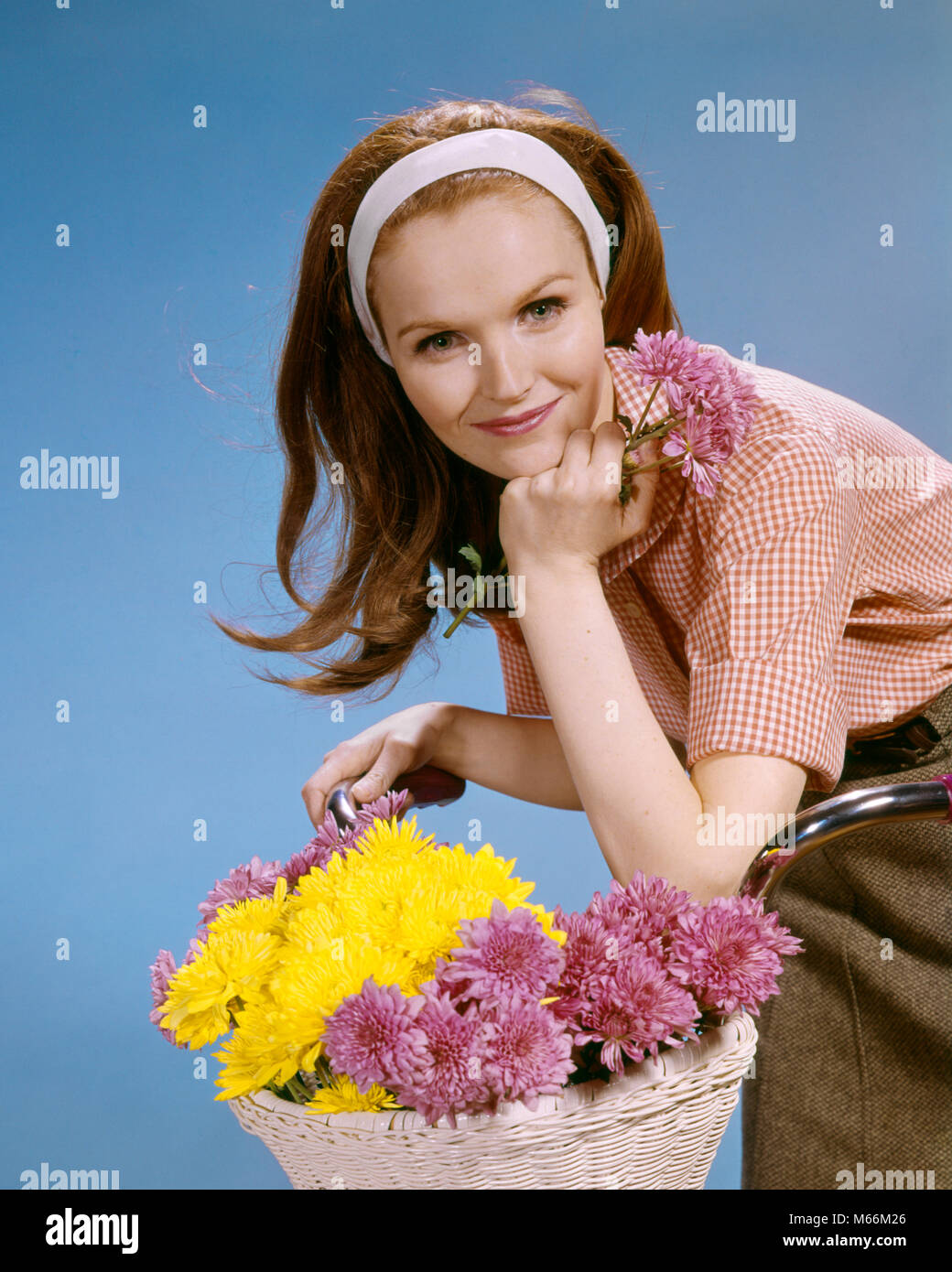 1960s SMILING REDHEAD YOUNG WOMAN RIDING BICYCLE WITH BASKET OF FLOWERS LOOKING AT CAMERA - kf5477 HAR001 HARS FEMALES - Stock Image