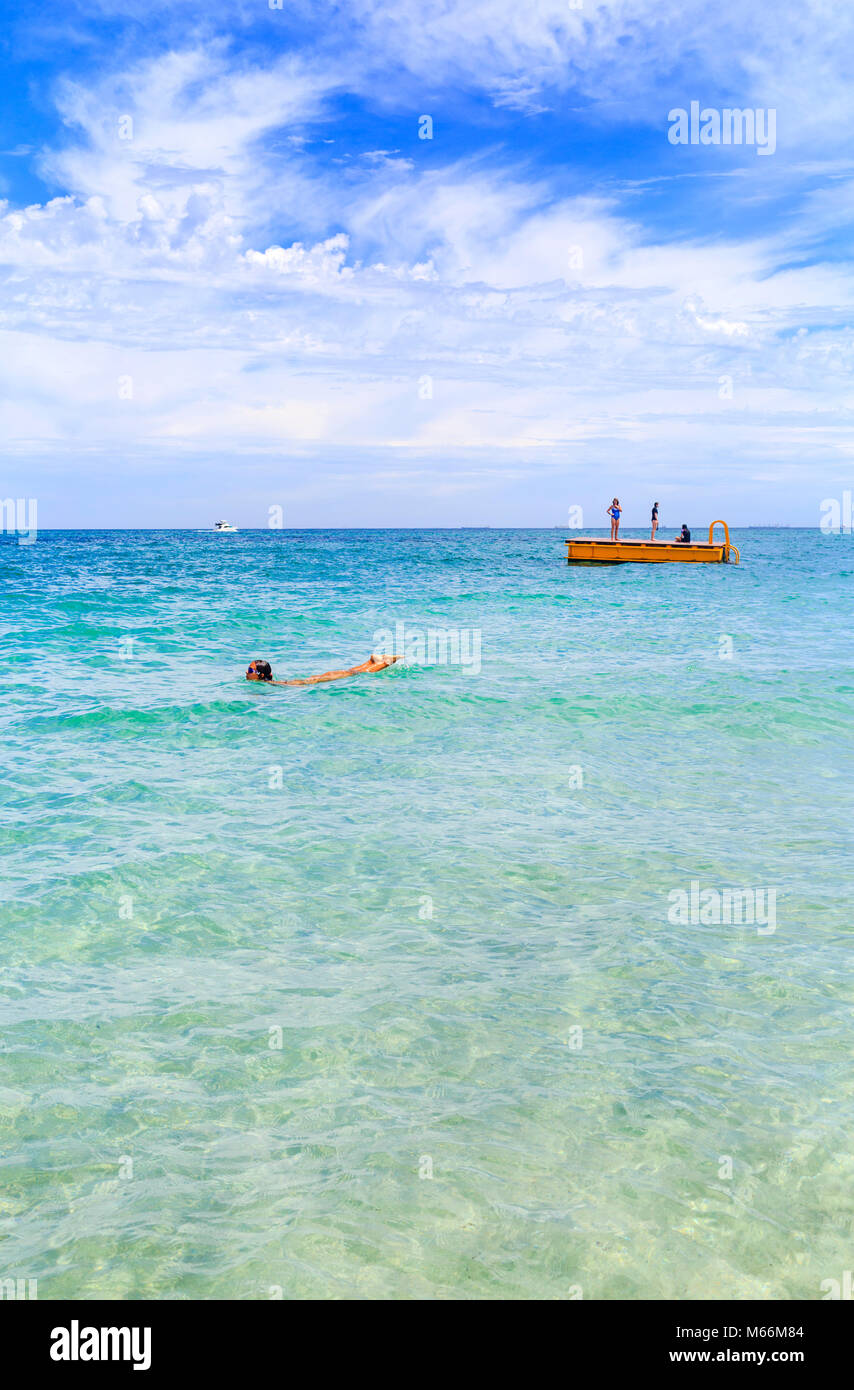 A woman swimming near the floating pontoon - Stock Image
