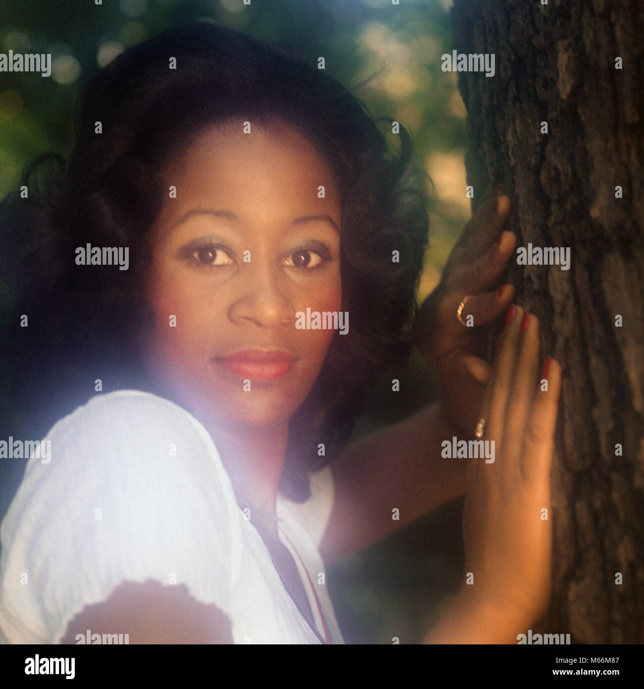 1970s PORTRAIT AFRICAN AMERICAN WOMAN OUTDOORS BY TREE LOOKING AT CAMERA - kg7565 HAR001 HARS LOOKING AT CAMERA - Stock Image