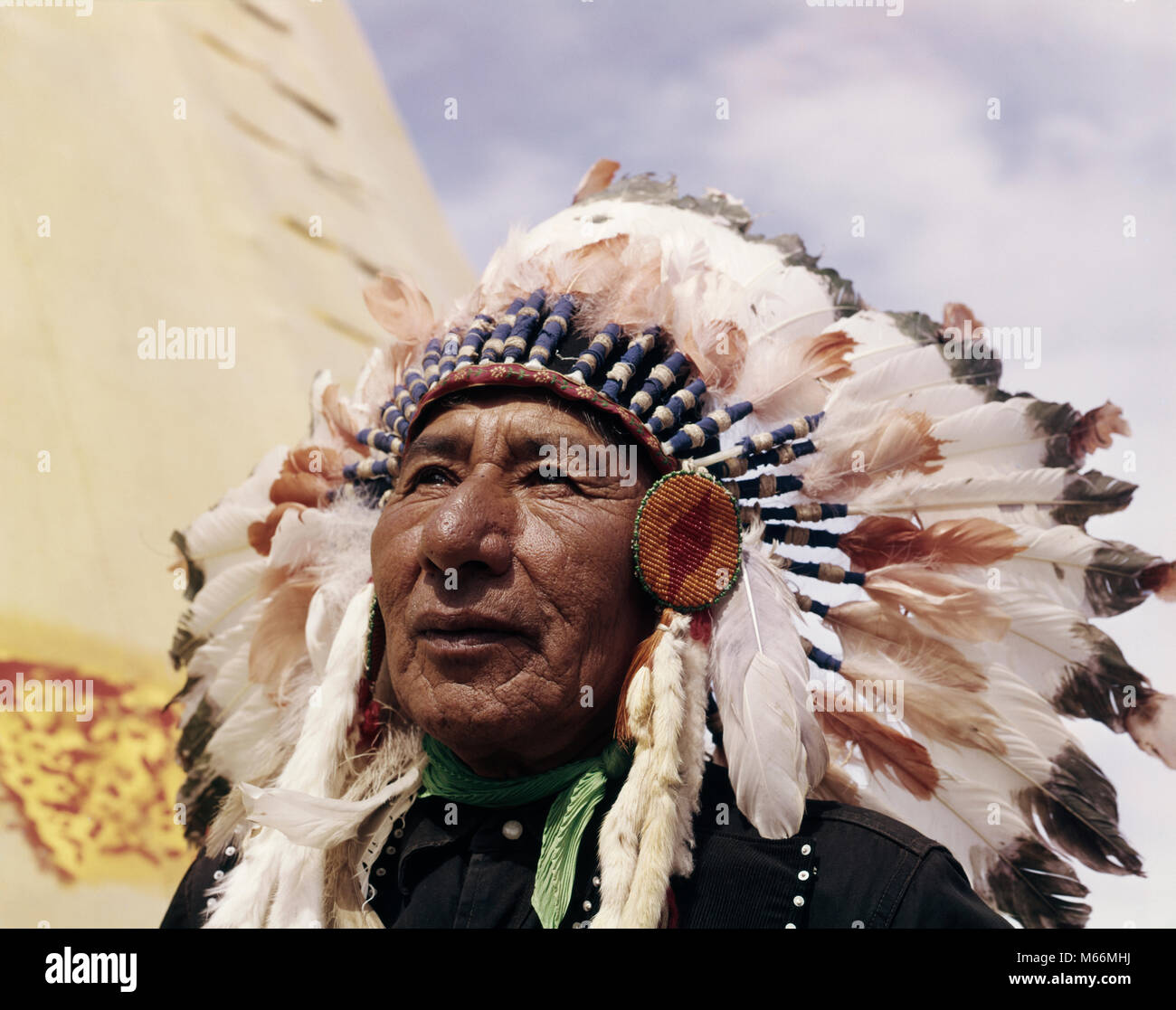 1960s NATIVE AMERICAN INDIAN MAN CHIEF GULL WEARING FEATHER BONNET MORLEY STONEY SIOUX FIRST NATIONS RESERVATION - Stock Image
