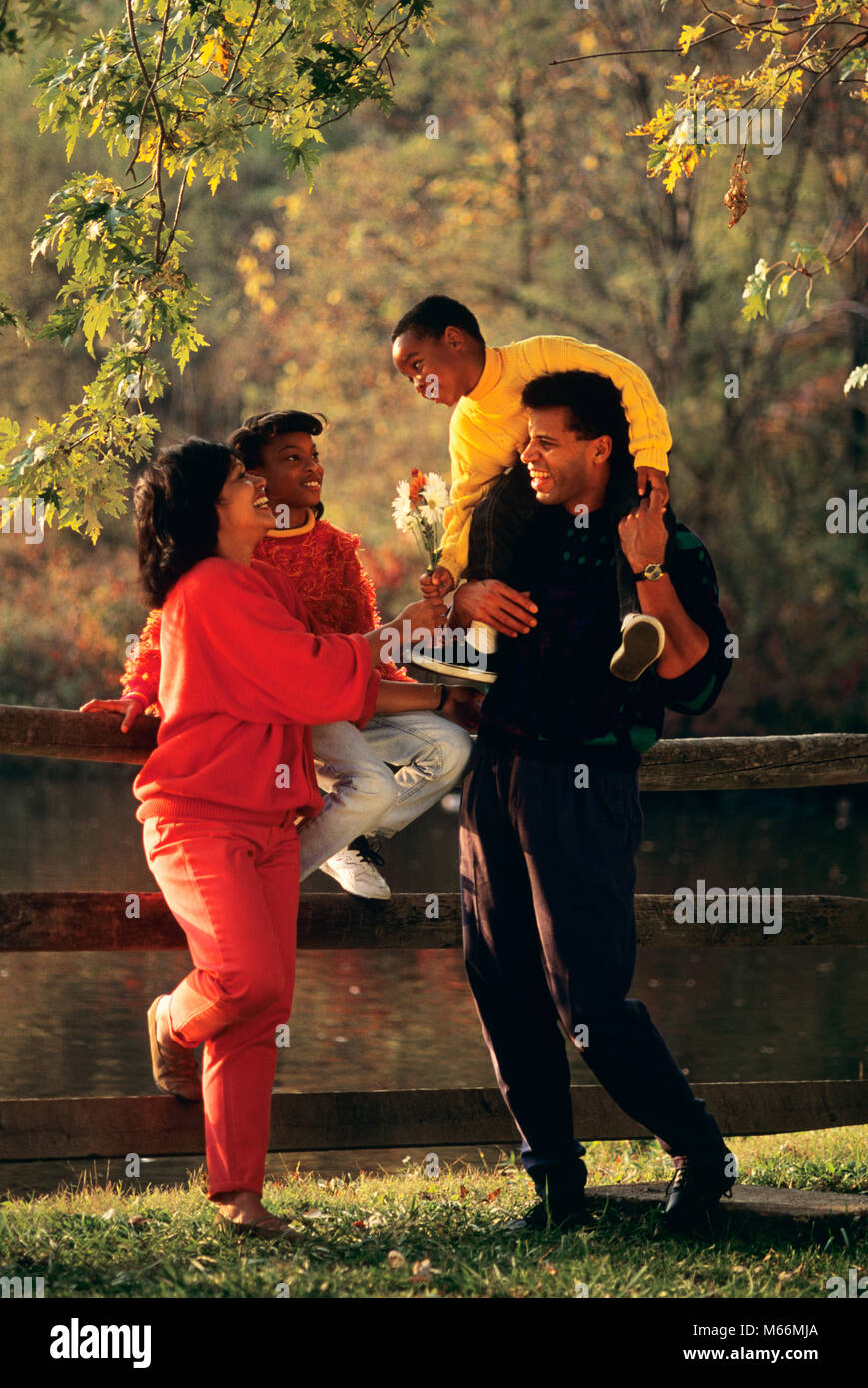 1990s AFRICAN AMERICAN FAMILY STANDING BY FENCE IN AUTUMN BOY HANDING FLOWERS TO MOTHER - kj12498 DEG002 HARS STAND - Stock Image