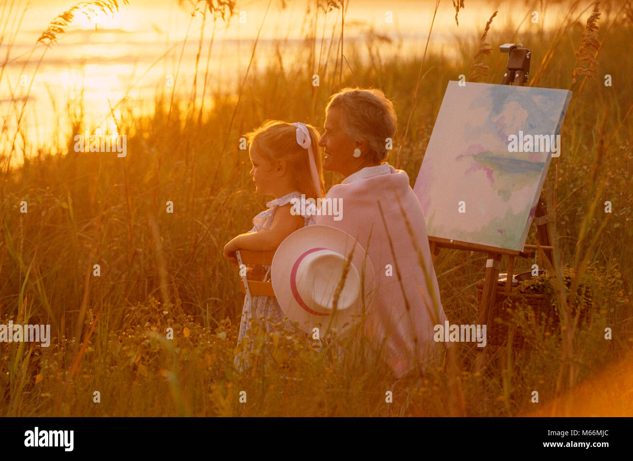1990s WOMAN ARTIST PAINTER AND GRANDDAUGHTER WITH CANVAS ON EASEL BY THE BEACH AT SUNSET - kj12541 LAF002 HARS PAINT - Stock Image